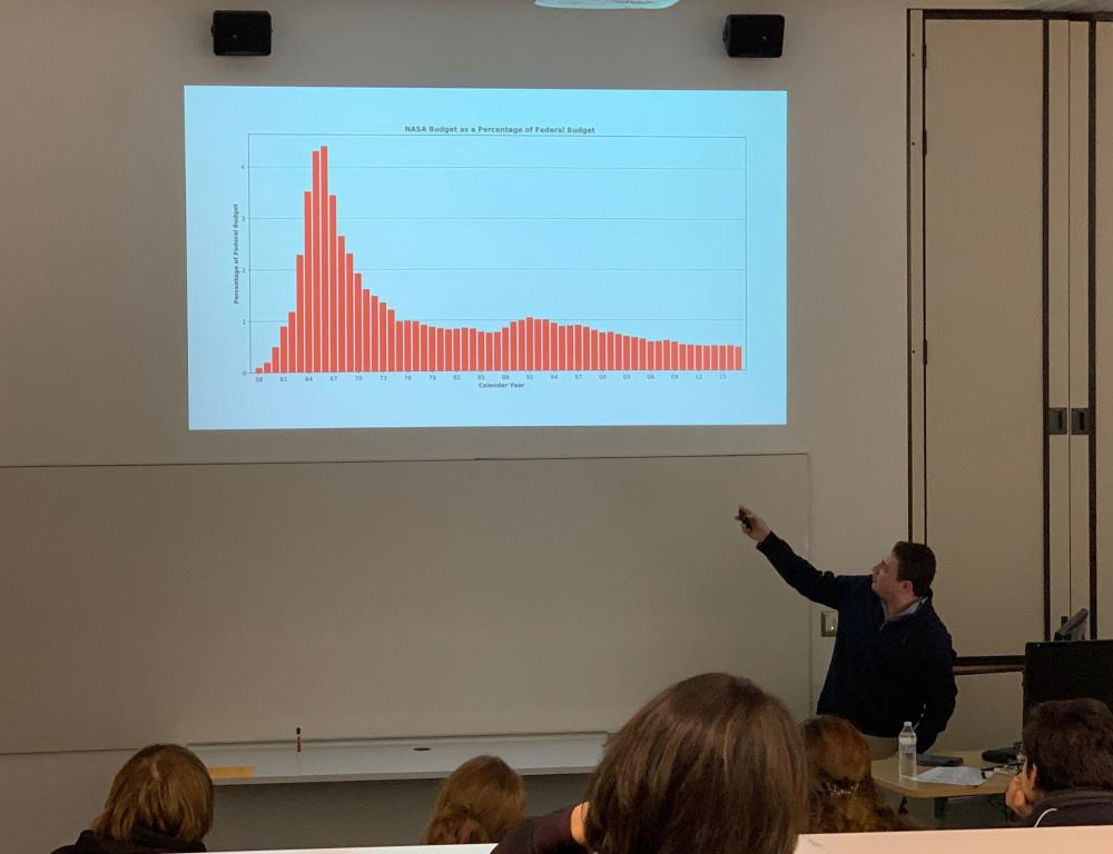 male student pointing to graph on slide projected above