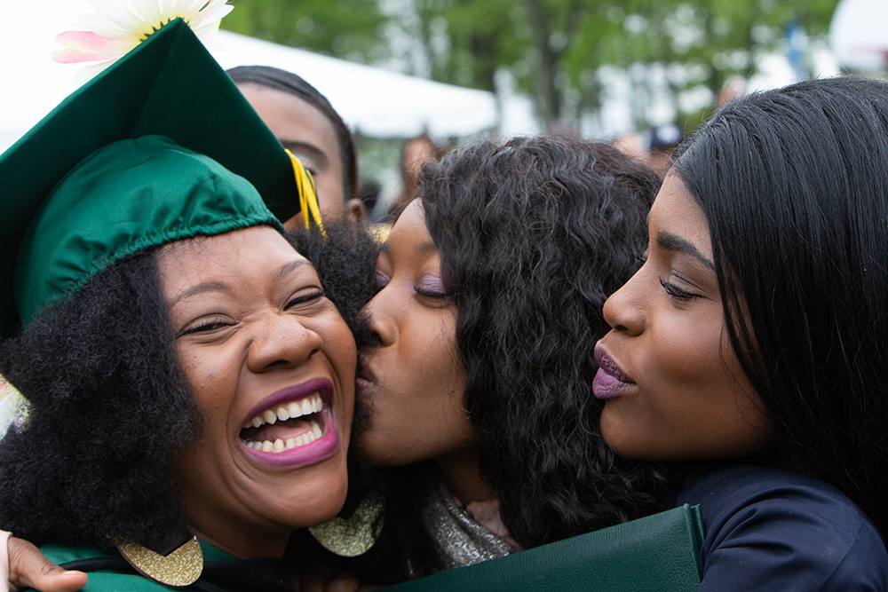 family kissing female grad