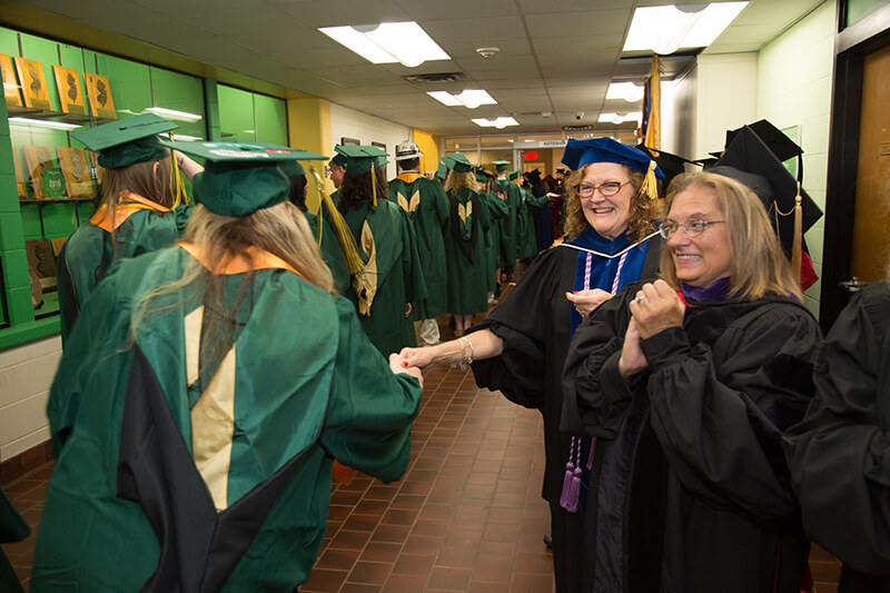 professor clutching hand of passing grad in line