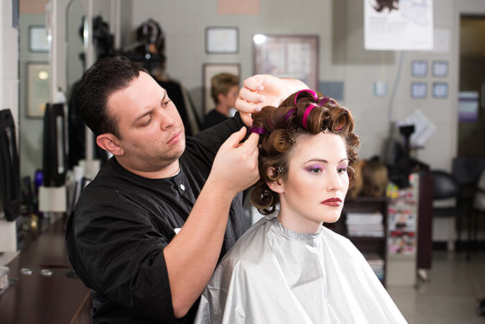 male student working on model's hair in rollers