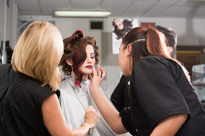 two women putting makeup on model