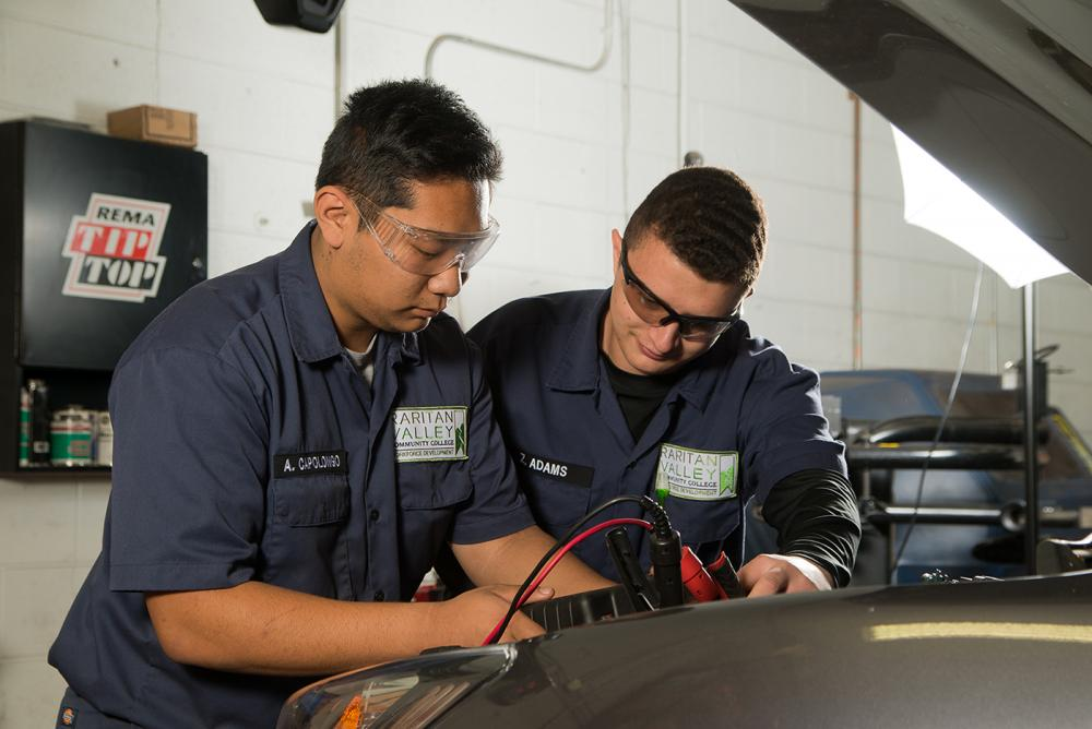 2 male students working on car