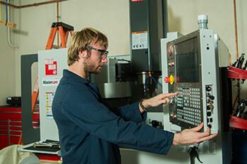 male student working on machine