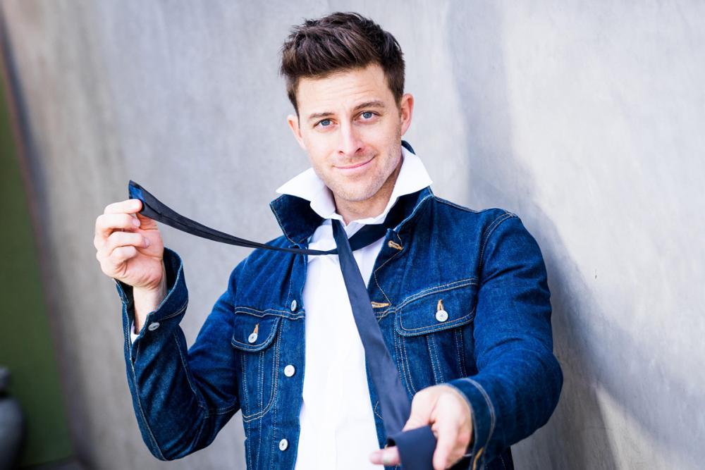 K-Von comedian in denim jacket holding tie
