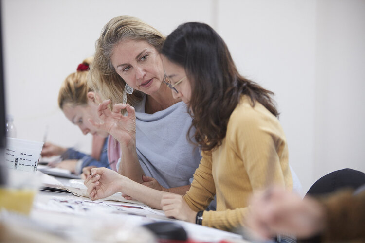 female teacher working with female student
