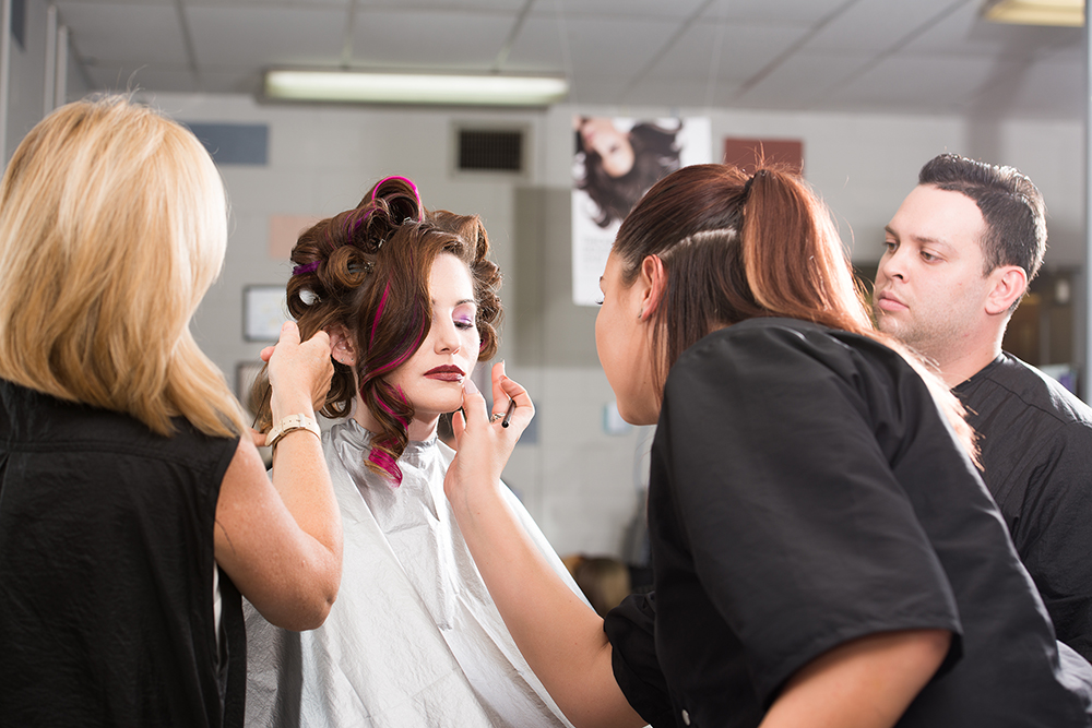 students work with makeup on model