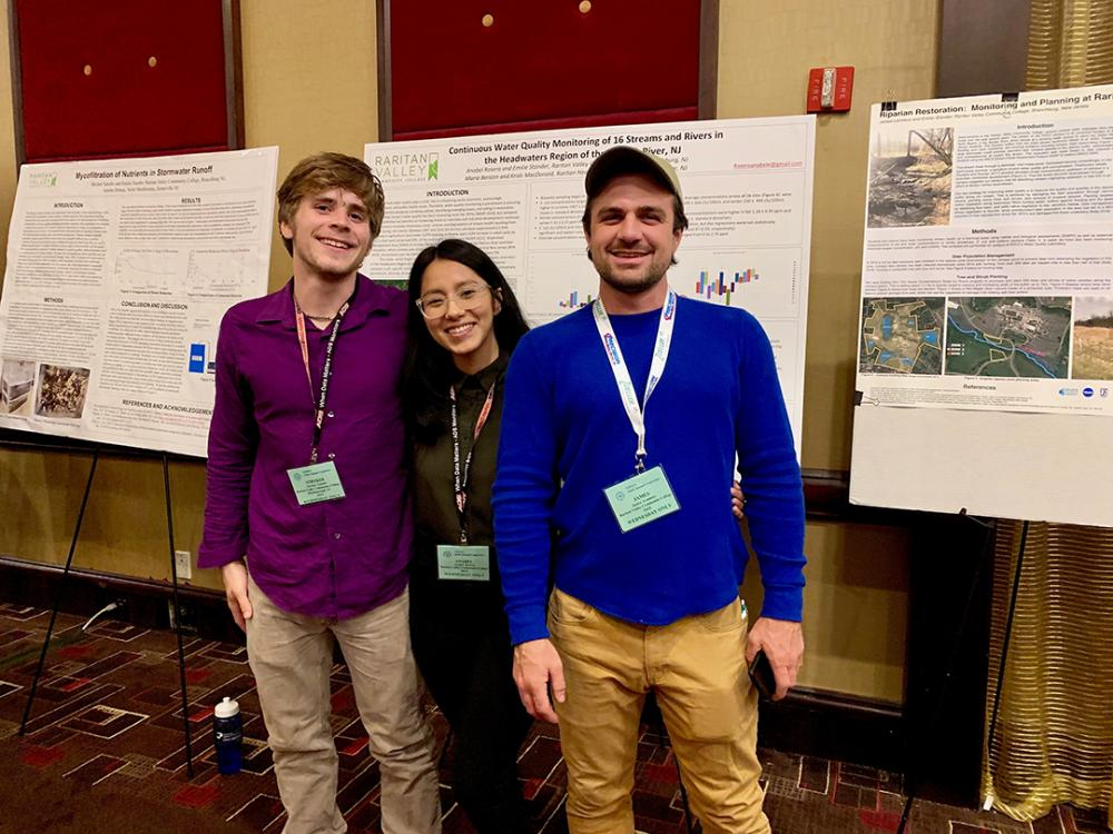3 students in front of posters at conference
