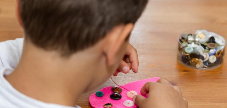 boy sewing buttons