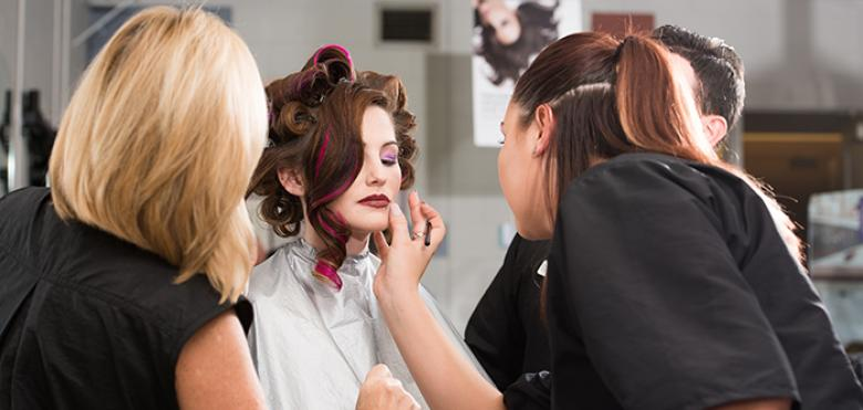 two women working on woman's makeup