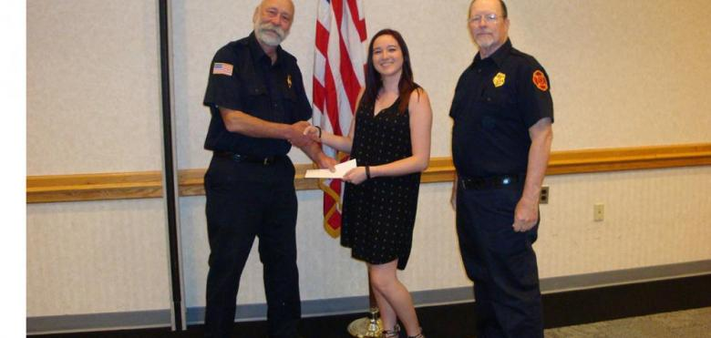 girl getting scholarship from fire police members