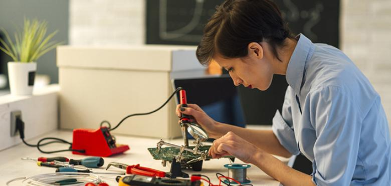 woman soldering circuit board
