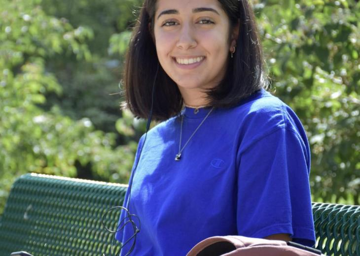 girl with dark brown hair outside on bench wearing bright blue shirt