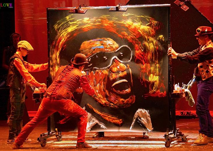 performers painting on a large canvas