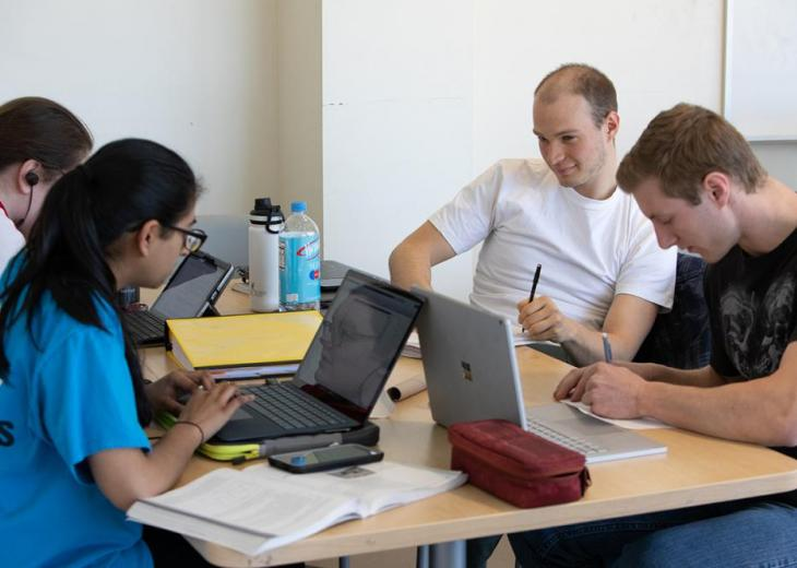 four students with laptops
