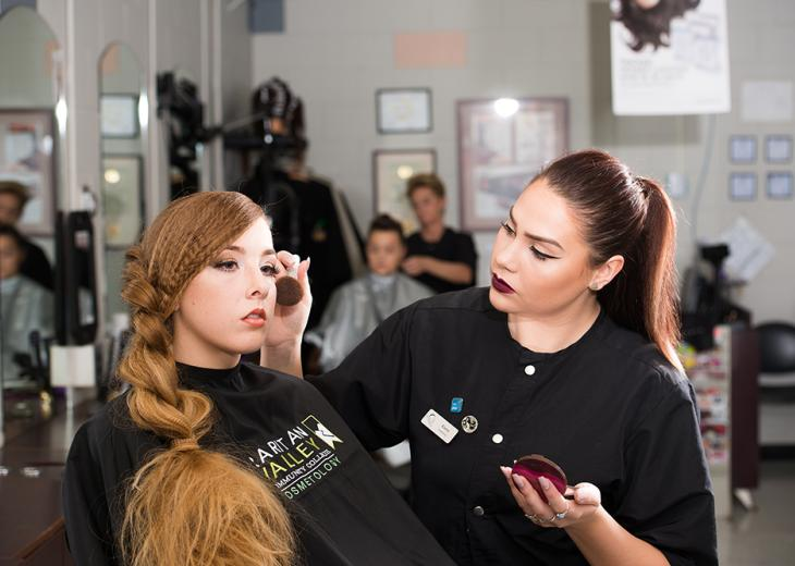 female student applying makeup on on another student