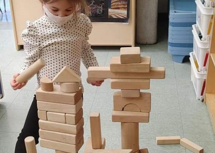 masked child playing with block tower