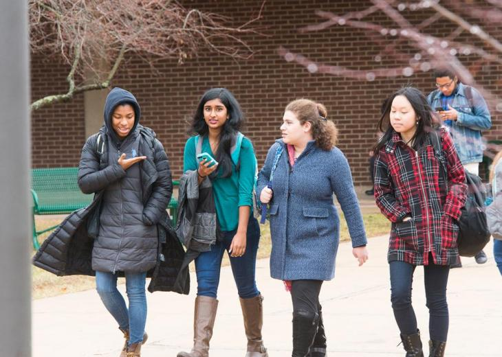 four female students walking outside together