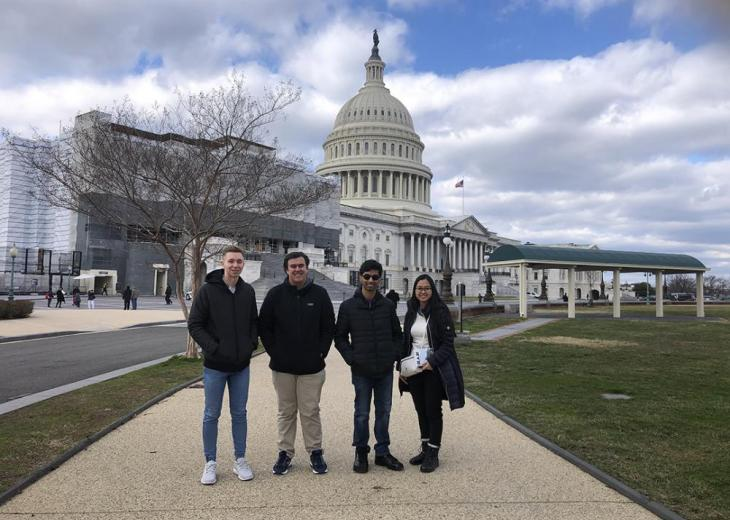 four students outside in front of capitol