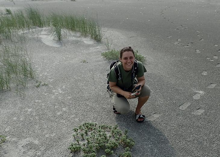 woman crouching down in sand with plants