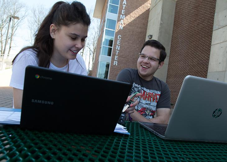 femal and male student outside with laptops