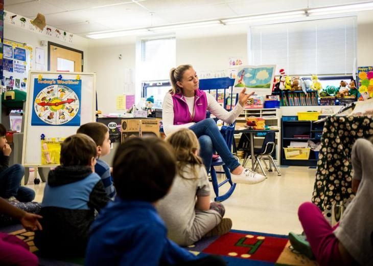 teacher on chair in classroom and backs of students