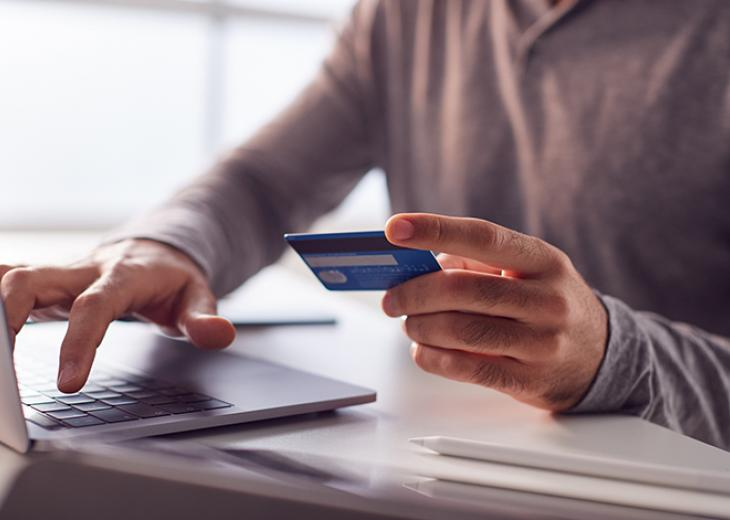 man holding credit card and typing on laptop