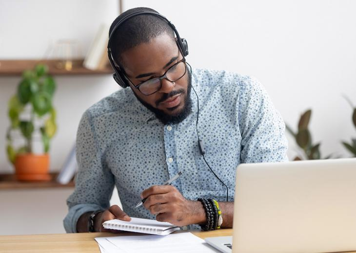 man wearing headphones taking notes and looking at tablet