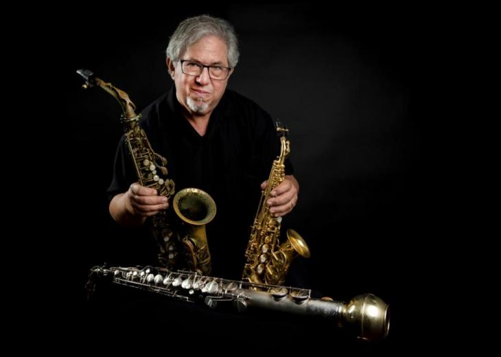 saxophone player paul cohen holding instruments
