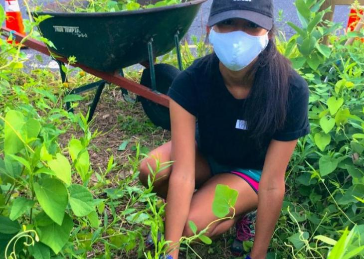 masked female student bending and planting