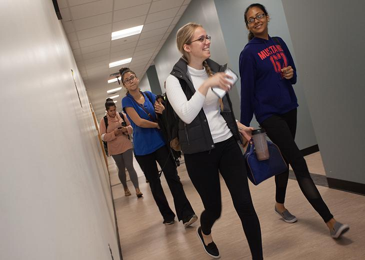 angular view of female students walking in hallway