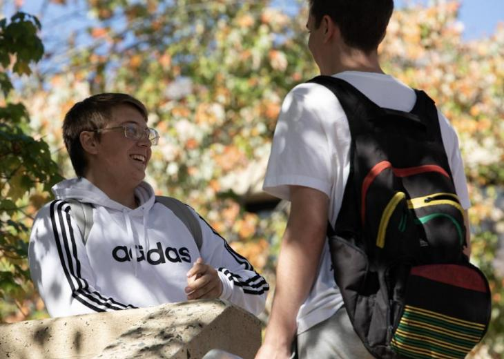 2 male students outside with one wearing backpack