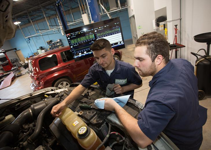 two auto tech students working on car