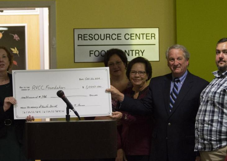five people with large check