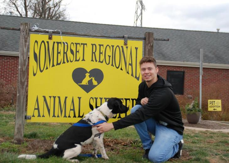 male student with dog outside animal shelter