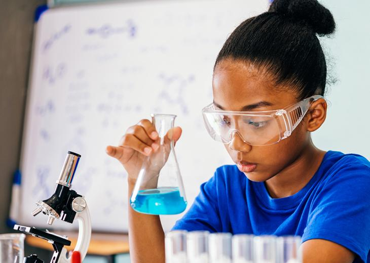 girl in protective glasses doing science experiment