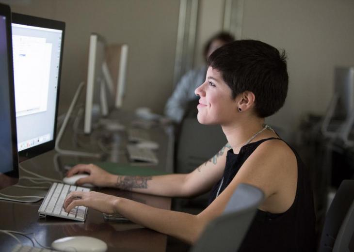 girl in sleeveless dark top on computer in lab