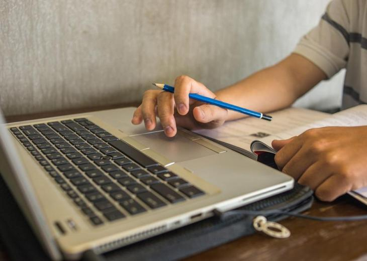 student holding pencil working on laptop