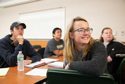 4 students in classroom with one smiling in front