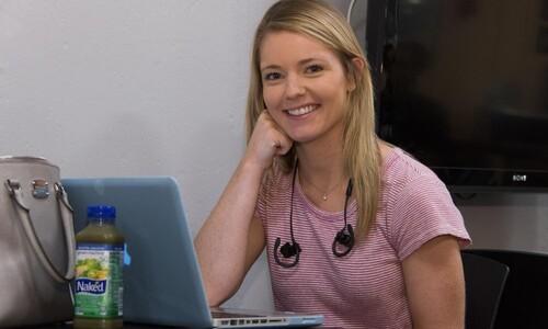 smiling girl with blonde hair wearing pink top using laptop