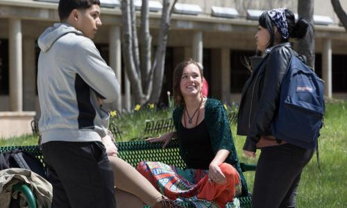 3 students outside on campus with one seated