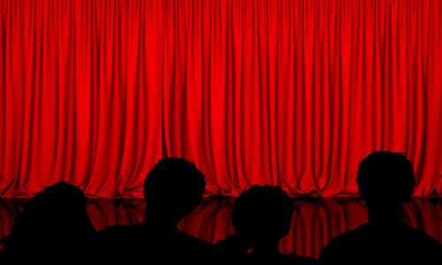 red curtain and backs of audience members heads