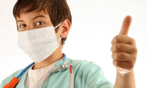 masked child doctor with thumb's up
