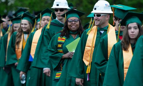 lines of grads, two males wearing hard hats