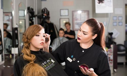cosmetology student applying blush to another student