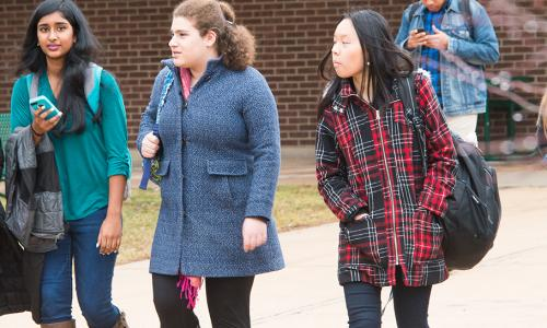 3 girls in coats walking outside with male student on phone