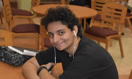 curly haired male student with headphones in ears