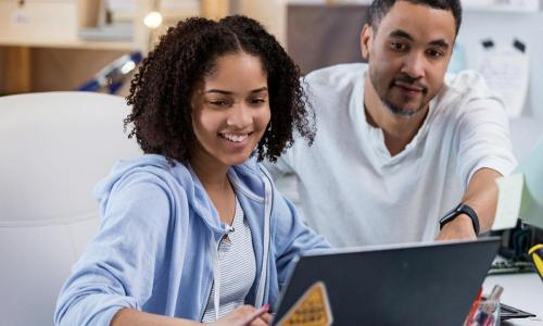 father helping tween girl on laptop