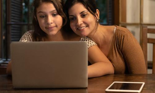 tween on laptop with mom close by