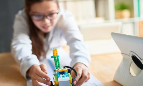 girl with robot using lego