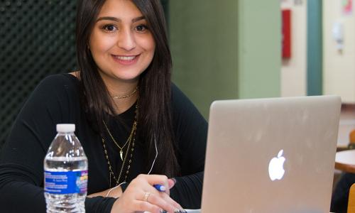 girl with brown hair on iMac with water bottle